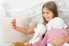 Flicka med modern teknologi för smartphonebruk Selfie med den favorit- leksaken Överför selfiefotoet dina vänner det sociala nätv royaltyfri bild