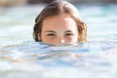 Flicka med munnen och näsan under vatten i simbassäng arkivfoton