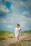 Flicka med nallebjörnen på naturbakgrund, blå himmel Arkivfoton
