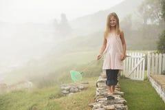 Flicka med netto balansera för fjäril på stenväggen Royaltyfri Fotografi