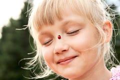Flicka med nyckelpigan på henne näsa arkivbilder