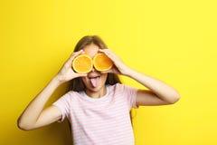 Flicka med orange frukt royaltyfria bilder