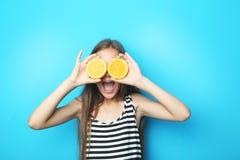 Flicka med orange frukt fotografering för bildbyråer