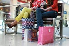 Flicka med påsar som går med hans flickvän på gallerian och att shoppa arkivbild