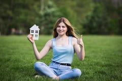 Flicka med pappdiagramet av huset Arkivfoto