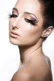 Flicka med perfekt hud och ovanlig makeup med fjädrar Härlig le flicka Royaltyfria Foton