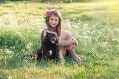 Flicka med pionen i hennes hår och svarta hund royaltyfri bild