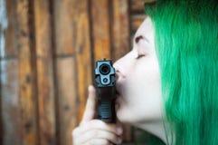 Flicka med pistolen och gräsplanhår Arkivbild
