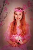 Flicka med rött hår i en rosa klänning och med blommor Fotografering för Bildbyråer
