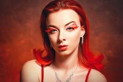 Flicka med rött hår och röda ögonfrans arkivfoto