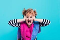 Flicka med rött hår som skrattar rymma hans huvud Tilltrasslat hår positiva sinnesrörelser härlig för studiokvinna för par dans s Arkivfoto