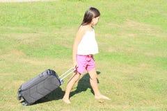 Flicka med resväskan Arkivbild
