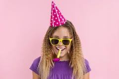 Flicka med rosa bakgrund, i festliga hattar som blåser i rören Royaltyfria Bilder