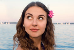 Flicka med rosa färgblomman vid vatten royaltyfri foto