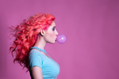Flicka med rosa hårtuggummi på en rosa bakgrund och Arkivbild