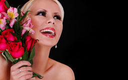 Flicka med rosor. lycklig ung kvinna med buketten av blommor över svart bakgrund, härlig blond le flicka Arkivbild