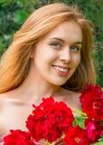 Flicka med rosor som ler utomhus Fotografering för Bildbyråer