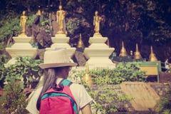 Flicka med ryggsäcken som skriver in till den buddistiska templet, Thailand royaltyfri foto