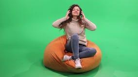 Flicka med sammanträde för lockigt hår på bönapåse och lyssnande musik stock video