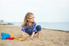Flicka med sand på havet Royaltyfri Fotografi