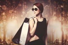 Flicka med shoppingpåsar på nattgatan Royaltyfri Foto