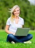 Flicka med silverbärbar datorsammanträde på gräset royaltyfria bilder