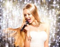 Flicka med sjunga för mikrofon Arkivfoto