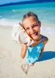 Flicka med skalet på stranden Arkivbilder