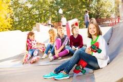 Flicka med skateboarden och henne sitta för kompisar Royaltyfri Foto