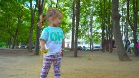 Flicka med skyffeln som spelar med sand lager videofilmer