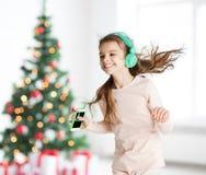 Flicka med smartphonen och hörlurar på jul arkivbild