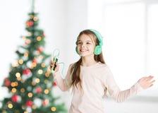 Flicka med smartphonen och hörlurar på jul Arkivfoto