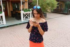 Flicka med smartphonen på den tomma gatan Arkivbilder