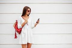 Flicka med smartphonen på gatan royaltyfri foto