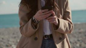 Flicka med smartphonen på havskust bara arkivfilmer