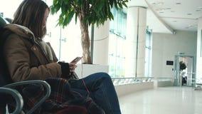 Flicka med smartphonen som väntar på en avvikelse stock video