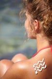 Flicka med solbränna och vågen av sollotion arkivfoto