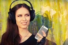 Flicka med stor hörlurar och den smarta telefonen på Grungebakgrund Arkivfoton