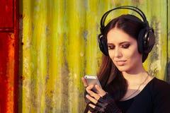 Flicka med stor hörlurar och den smarta telefonen på Grungebakgrund Royaltyfria Foton