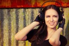 Flicka med stor hörlurar på Grungebakgrund Arkivbild