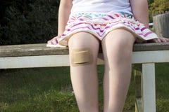 Flicka med stor murbruk på hennes knä Arkivfoto