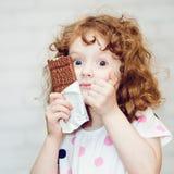 Flicka med stora blåa ögon som rymmer greedily choklad på ljusa lodisar Royaltyfria Bilder