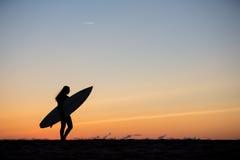 flicka med surfingbrädan i solnedgång på stranden Royaltyfri Foto