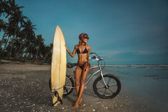 Flicka med surfingbrädan och cykeln på stranden Royaltyfria Bilder