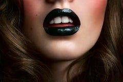 Flicka med svarta kanter och vita tänder Arkivbild