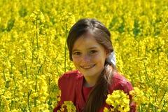 Flicka med tand- hänglsen i ett fält med gula blommor royaltyfri bild