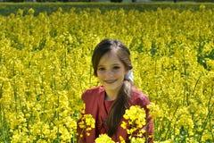Flicka med tand- h?nglsen i ett f?lt med gula blommor arkivbild