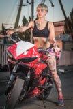 Flicka med tatueringar som sitter på en motorcykel Arkivfoto