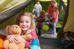Flicka med Teddy Bear Enjoying Camping Holiday på campingplats Royaltyfri Bild