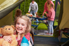 Flicka med Teddy Bear Enjoying Camping Holiday på campingplats royaltyfri bild
